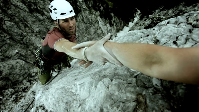 hd: climber reaching for a helping hand - strength stock videos & royalty-free footage