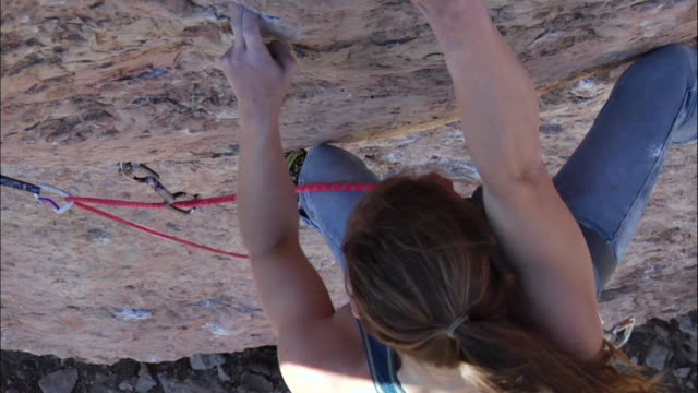 vidéos et rushes de cu ms of climber she makes difficult moves on steep rock face. climber clips on rope into rock for protection / canon city / shelf road,co,usa - corde
