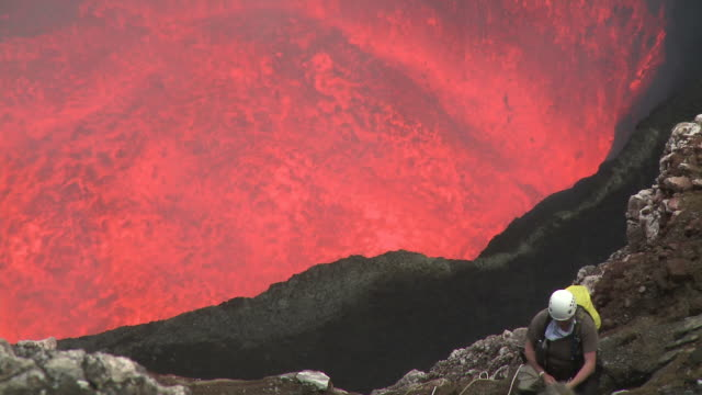 climber stands on ledge above dangerously erupting lava, marum volcano, ambrym island, vanuatu - geologist stock videos & royalty-free footage
