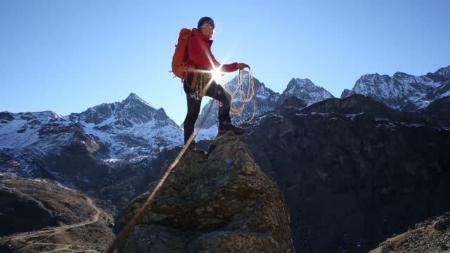 Climber stands on pinnacle summit, pulls rope in to companion
