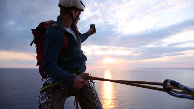 climber stops during rappel (abseil) to take pic of view over sea - スポーツヘルメット点の映像素材/bロール