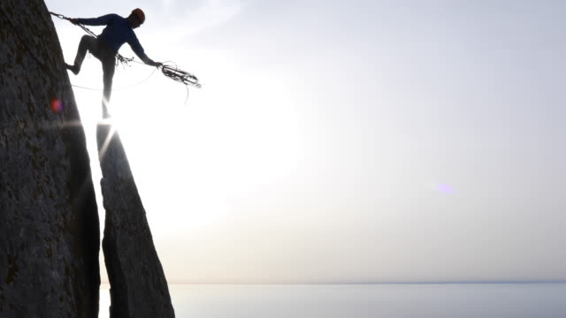 climber throws rope out for rappel, sea below - climbing rope stock videos & royalty-free footage