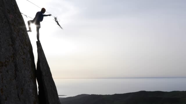 Climber tosses rope from vertical rock flake