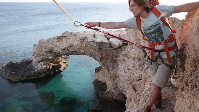 Climber traverses narrow ledge above sea