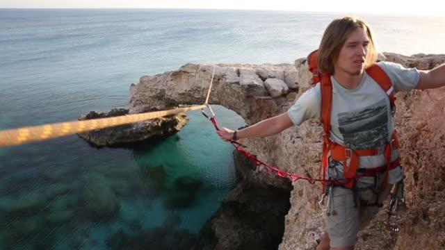 climber traverses narrow ledge above sea - t shirt stock videos & royalty-free footage