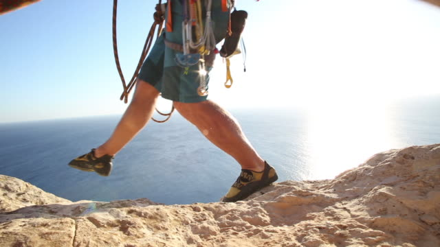 Climber traverses narrow ridge, above sea