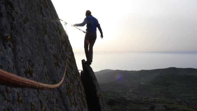 climber traverses vertical cliff, ascends rock flake - der weg nach vorne stock-videos und b-roll-filmmaterial