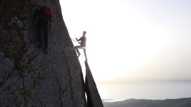 Climber traverses vertical cliff, towards teammate
