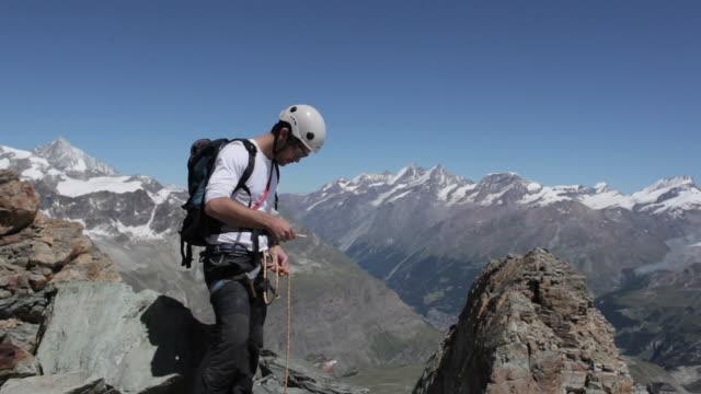 vidéos et rushes de climber tying rope into his harness in the mountains - harnais de sécurité