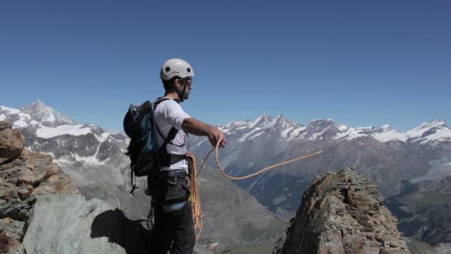 vídeos y material grabado en eventos de stock de climber tying rope into his harness in the mountains - accesorio de cabeza