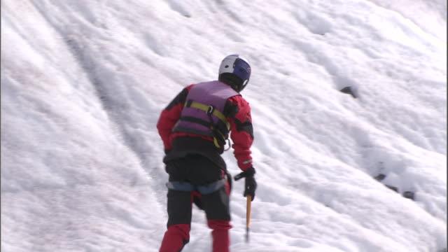 vídeos y material grabado en eventos de stock de a climber uses crampons as he climbs an icy  hillside. - accesorio de cabeza
