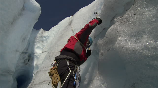 a climber uses special equipment to ascend a steep cliff covered with ice and snow. - climbing stock videos & royalty-free footage