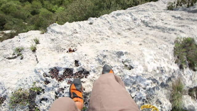 Climber walks across ledge, looks over cliff edge to valley below