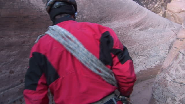 stockvideo's en b-roll-footage met a climber walks through water in a stone crevice. - crevice