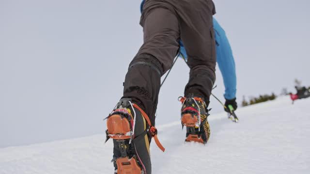 vídeos y material grabado en eventos de stock de escalador con un hacha de hielo escalando montaña nevada - nevosa