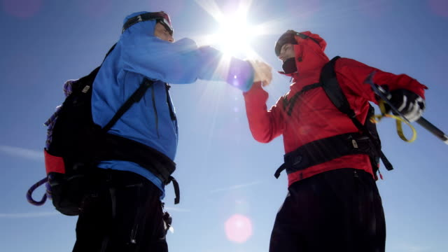 Climbers are shaking hands on a mountain peak