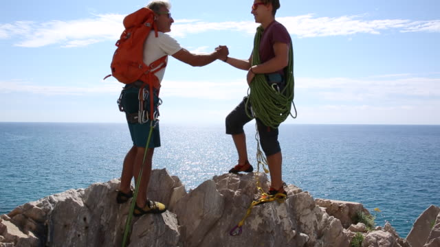 vidéos et rushes de climbers arrive at top of steep cliff, exchange hand shake - amitié masculine