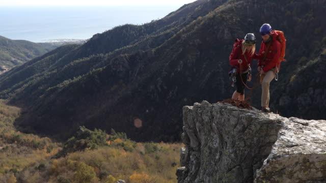 climbers ascend rock ridge, above valley, sea - sports helmet stock videos & royalty-free footage