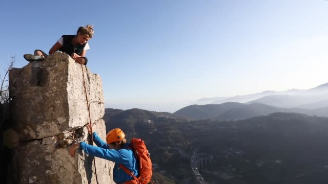 climbers ascend vertical rock pinnacle - sports helmet stock videos and b-roll footage