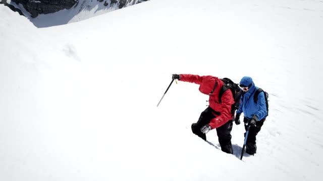 vídeos y material grabado en eventos de stock de escaladoras subirse a una montaña de nieve-cubierta - en lo alto posición descriptiva