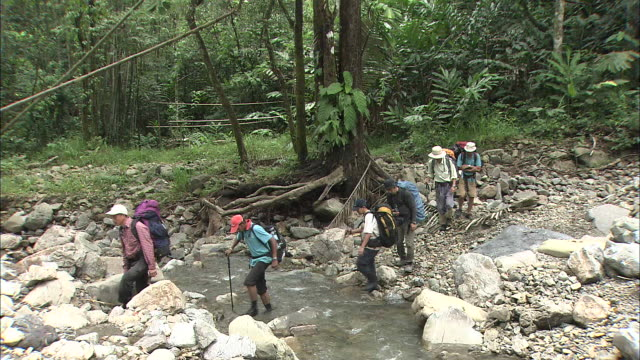 Climbers Crossing River In Malaysia