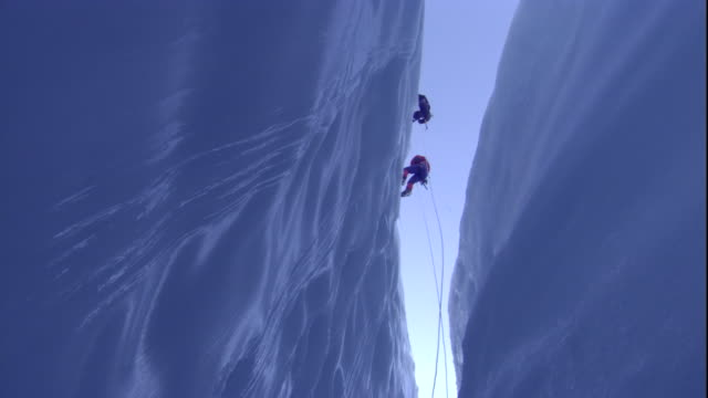 Climbers descend into entrance of moulin fissure in glacier, Switzerland. Available in HD.