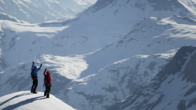 stockvideo's en b-roll-footage met climbers exultant on a snow-covered mountain peak - bergketen