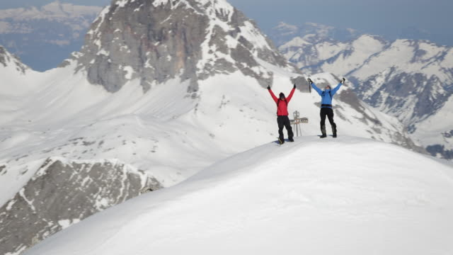 Climbers exultant on a snow-covered mountain peak