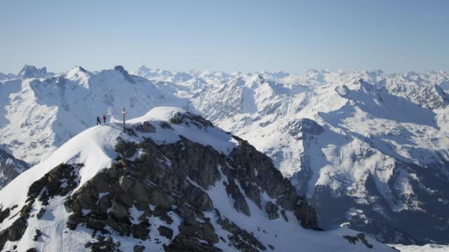 climbers exultant on a snow-covered mountain peak with a cross on it - bergstopp bildbanksvideor och videomaterial från bakom kulisserna