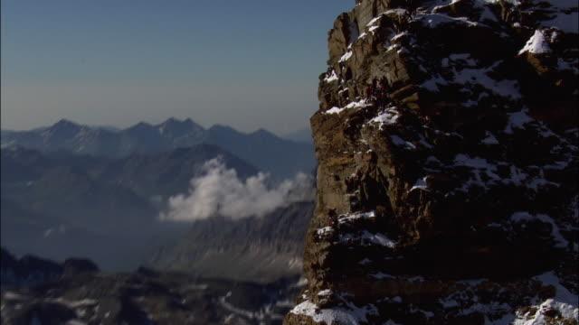 vídeos de stock, filmes e b-roll de climbers going up along h??rnli ridge, matterhorn, with a help of fixed rope - corda de escalada