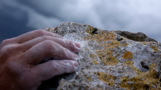 Climber's hands grapple with final rock holds