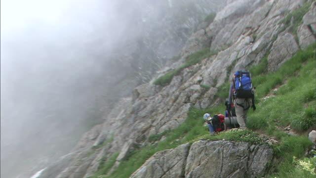 Climbers hike on Mt. Tsurugidake as the mist rolls in.