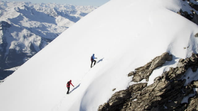 stockvideo's en b-roll-footage met climbers on a snow-covered mountain - bergketen