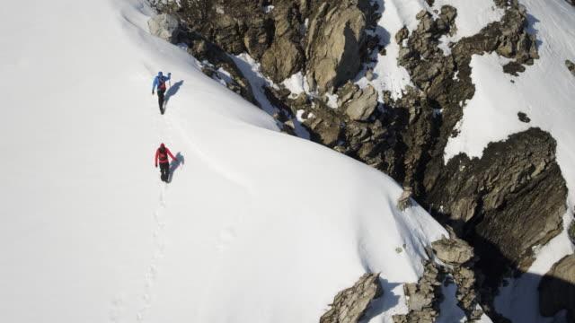 vídeos de stock e filmes b-roll de alpinistas em uma montanha coberta de neve - risco