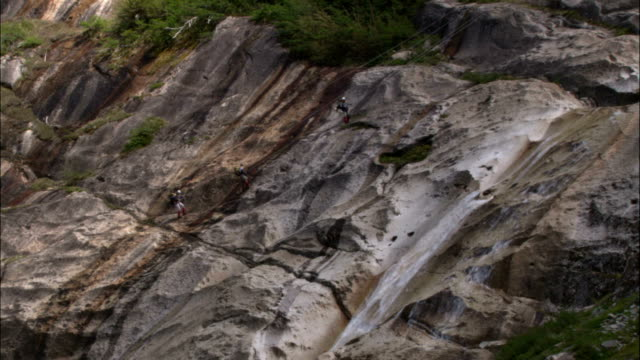 climbers rappel down a rock face next to a waterfall. - rock face stock videos & royalty-free footage
