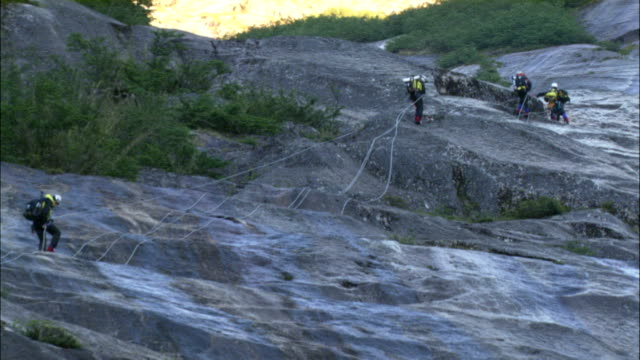 climbers rappel down a rock face. - rock face stock videos & royalty-free footage