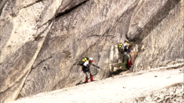climbers rappel down a smooth rock face. - rock face stock videos & royalty-free footage