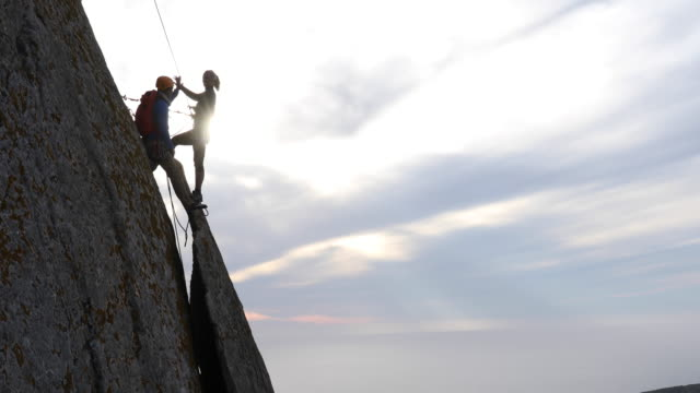 Climbers stand on rock flake, arranging ropes