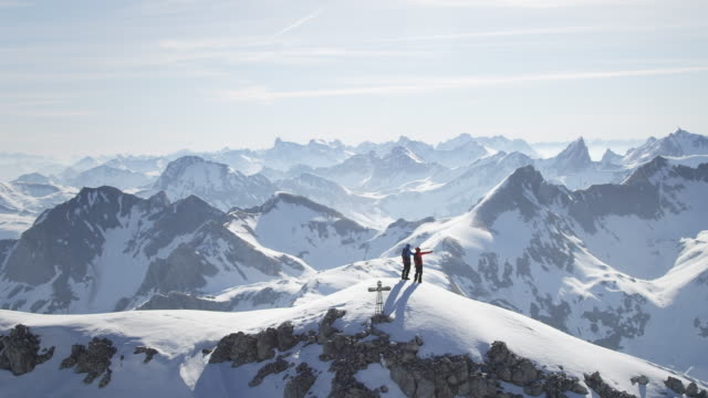 climbers standing on a snow-covered mountain peak - mountain peak stock videos and b-roll footage