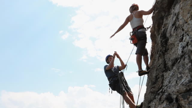 climbers take picture while hanging from rock wall - abseiling stock videos & royalty-free footage
