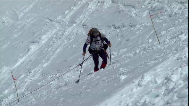 climbers use ski poles and rope on a steep slope. - bastoncino da sci video stock e b–roll