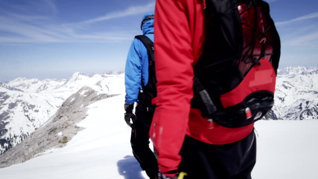Climbers walk on a snow-covered mountain peak