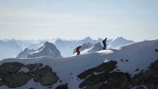 climbers walk on a snow-covered mountain - mountain peak stock videos and b-roll footage