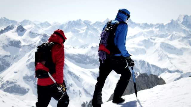 vídeos y material grabado en eventos de stock de escaladoras a pie sobre una montaña de nieve-cubierta - escalada