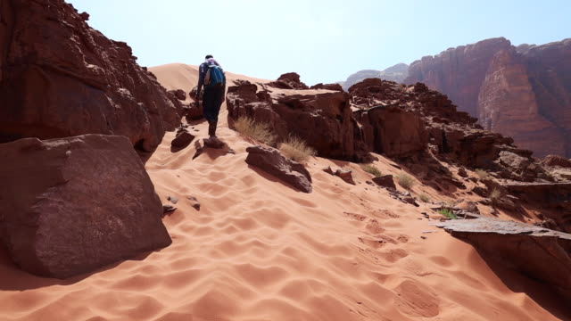 climbing a hill in the stunning landscape of the wadi rum. - sand dune stock videos & royalty-free footage
