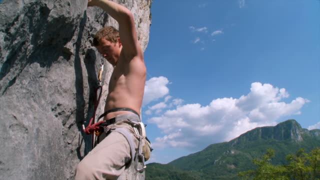 hd crane: climbing a rock wall - climbing wall stock videos and b-roll footage