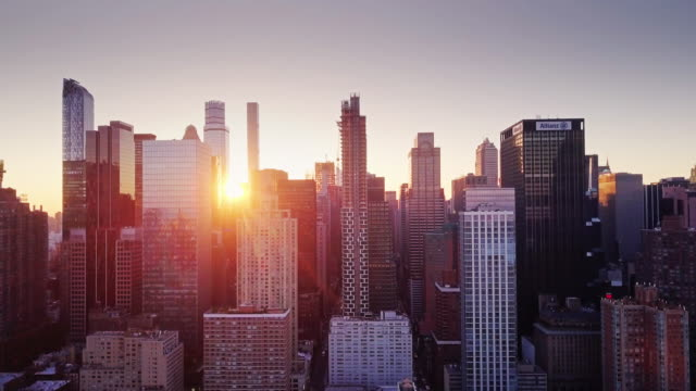 vidéos et rushes de climbing aerial view over manhattan with rising sun between skyscrapers - quartier de bureaux