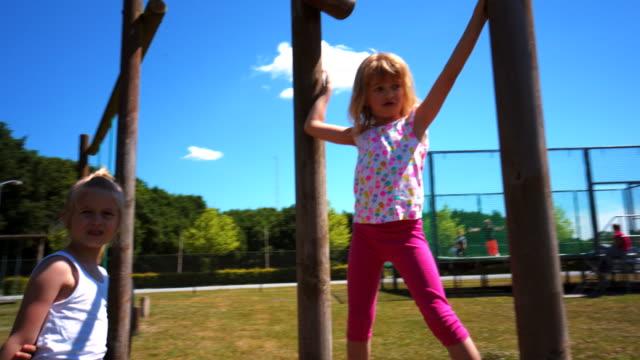 klettern und spielen in einem park-spielplatz - kind im grundschulalter stock-videos und b-roll-filmmaterial