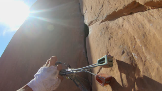 climbing pov as rock climber inserts spring-loaded camming device into crack on rock face. - imbracatura di sicurezza video stock e b–roll