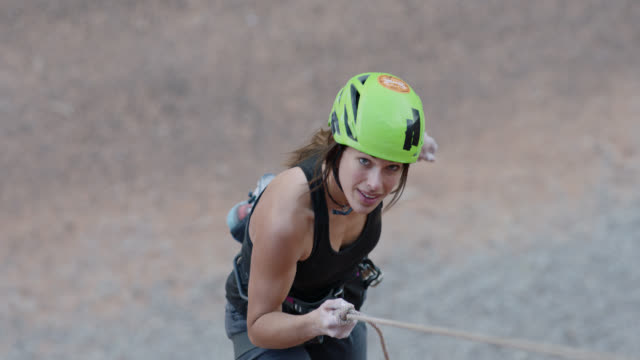 SLO MO. Climbing chalk blows in the wind as young woman rappels down rock face.